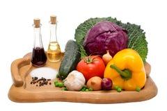 Cetriolo, pepe, cipolla, aglio, foglie del cavolo, pomodoro e cavolo rosso su un plateau con petrolio, aceto, pepe e sale Immagini Stock Libere da Diritti