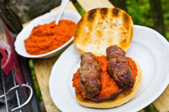 Cevapcici with ajvar in the grilled roll Stock Photos