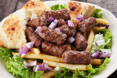 Cevapcici, bosnian minced meat kebab. With onion and french fries Royalty Free Stock Photography