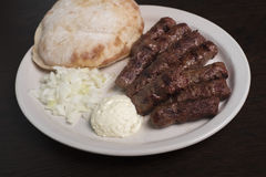 Cevapi Lepinja. Portion of Cevapi with homemade bun served with onion and traditional cheese spread Kajmak Stock Image