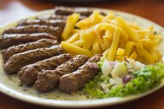 Cevapi, serbian traditional food. Cevapi, traditional serbian speciality with french fries, green salad and onion stock image