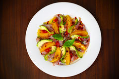 Ceviche salad with raw fish, avocado and orange. Ceviche salad with raw fish, avocado, orange, chili and sesame seeds on wooden table Royalty Free Stock Photography