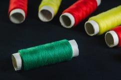 Cewy zieleni, czerwieni i koloru żółtego nici na czarnej tkaninie, zdjęcia royalty free
