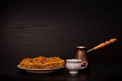 Cezve, κούπα καφέ και ένα πιάτο του παραδοσιακού τουρκικού γλυκού baklava σε ένα μαύρο υπόβαθρο διάστημα αντιγράφων Στοκ εικόνα με δικαίωμα ελεύθερης χρήσης