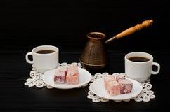 Cezve, bunte türkische Freude und zwei Tasse Kaffees auf den Spitzeservietten schwärzen Hintergrund Lizenzfreies Stockfoto