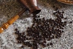 Cezve con los granos y las crepes derramados de café con las patatas hervidas en el fondo fotografía de archivo