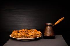 Cezve de café et d'un plat de baklava avec du miel sur un fond noir Photo stock