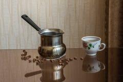 Cezve en kop van vers gebrouwen koffie die zich op een glaslijst bevinden royalty-vrije stock foto's
