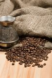 Cezve with freshly roasted coffee beans on table Stock Photography