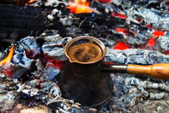 Cezve with hot flavored coffee on a bonfire closeup. Stock Photo