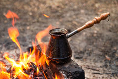 Cezve with hot flavored coffee on a bonfire closeup. Royalty Free Stock Photo