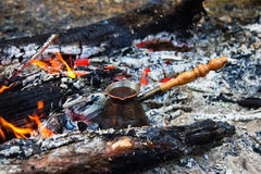 Cezve with hot flavored coffee on a bonfire. Stock Photos