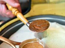 Cezve (ibrik) coffee. Metal cezve (ibrik) in hot sand during coffee preparation stock photos