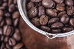 Cezve, ibrik full of coffee beans. Saucepan for coffee and coffee beans closeup royalty free stock images