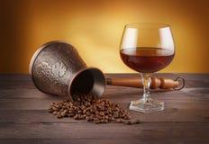 Cezve mit Kaffeebohnen und Glas Whisky Stockbilder