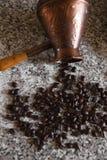 Cezve mit verschütteten Kaffeebohnen und Pfannkuchen mit gekochten Kartoffeln im Hintergrund lizenzfreie stockfotos