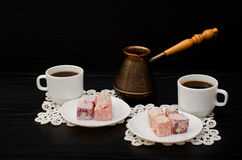 Cezve, plaisir turc coloré et deux tasses de café sur le fond noir de serviettes de dentelle Photo libre de droits