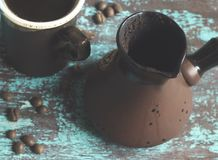 A cezve is a pot designed specifically to make Turkish coffee. A cezve is a pot to make Turkish coffee and coffee beans on blue background royalty free stock images