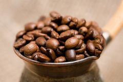 Cezve with roasted coffee beans on sackcloth Stock Images