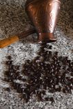 Cezve with spilled coffee beans and pancakes with boiled potatoes in the background royalty free stock photos
