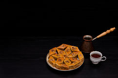 Cezve, tasse de café et un plat de baklava douce turque traditionnelle Copiez l'espace, fond noir Photographie stock