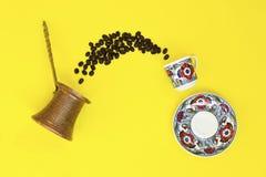 Cezve turc, grains de café dans la tasse d'expresso sur le fond jaune photographie stock libre de droits
