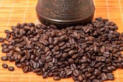 Cezve und Kaffeebohnen auf Bambusmatte Stockbild