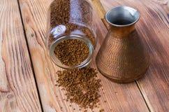 Cezve volcado con los granos de caf?, cuenco con el caf? molido en la tabla de madera fotografía de archivo libre de regalías