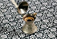 Cezve z świeżo warzącą kawą na tradycyjnych ornamentach Fotografia Royalty Free