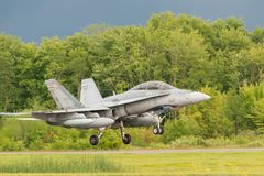 CF18 above runway. PETERBOROUGH, ON, CANADA - JULY 14, 2017: A Canadian Forces CF18 lands at Peterborough airport. The aircraft was part of Peterborough`s Canada Stock Photo