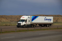 CFI / Conway Truckload. A white CFI Semi Pulls a white Conway Truckload trailer along a rural Wyoming interstate Royalty Free Stock Photography