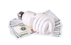CFL与金钱美元现金的荧光灯电灯泡 免版税库存照片