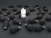 Cfl an Eco energy saving light bulb,. One glowing compact fluorescent light bulb standing out Stock Photo