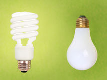 CFL and regular bulbs on green. Compact fluorescent energy saving environment friendly and old fashioned regular bulb on green background Royalty Free Stock Photo