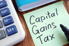 CGT资本收益税 备忘录棍子和计算器 免版税库存照片