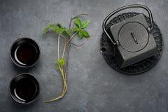 Chá asiático em um bule preto e em uns copos do ferro fundido Estilo asiático Imagens de Stock