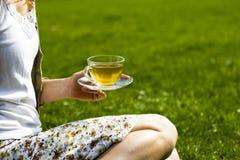 Chá bebendo da jovem mulher na grama Foto de Stock Royalty Free