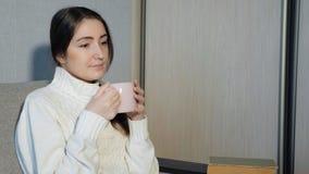 Chá bebendo da menina bonita e leitura de um livro no sofá fotografia de stock