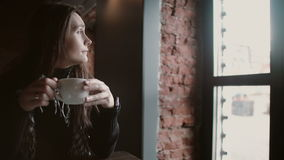 Chá bebendo da moça de uma caneca e de olhar para fora a janela que senta-se no sótão moderno que janta 4k Foto de Stock