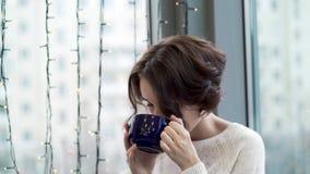 Chá bebendo da mulher bonita e vista para fora da janela com festões Conforto morno do inverno A mulher olha para fora a espera d filme