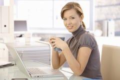 Chá bebendo da mulher de negócios nova no escritório imagem de stock royalty free