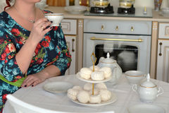 Chá bebendo da mulher do russo com os marshmallows doces na mesa de cozinha Fotografia de Stock Royalty Free