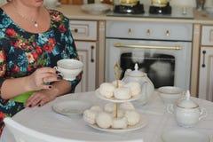 Chá bebendo da mulher do russo com os marshmallows doces na mesa de cozinha Fotos de Stock Royalty Free