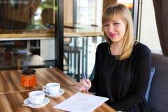Chá bebendo da mulher e trabalho com papéis de negócio Foto de Stock