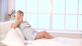Chá bebendo da mulher gravida ao encontrar-se na cama em casa video estoque