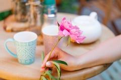 Chá bebendo de assento da mulher em um café com flor à disposição Fotos de Stock Royalty Free