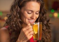 Chá bebendo do gengibre da jovem mulher feliz com limão imagem de stock