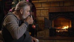 Chá bebendo do homem superior perto da chaminé na Noite de Natal filme