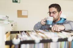 Chá bebendo do trabalhador de escritório quando olhar arquivar no trabalho foto de stock royalty free
