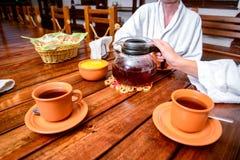 Chá bebendo dos pares novos felizes com mel no hotel após o roupão branco vestindo do procedimento saudável da recreação Imagens de Stock